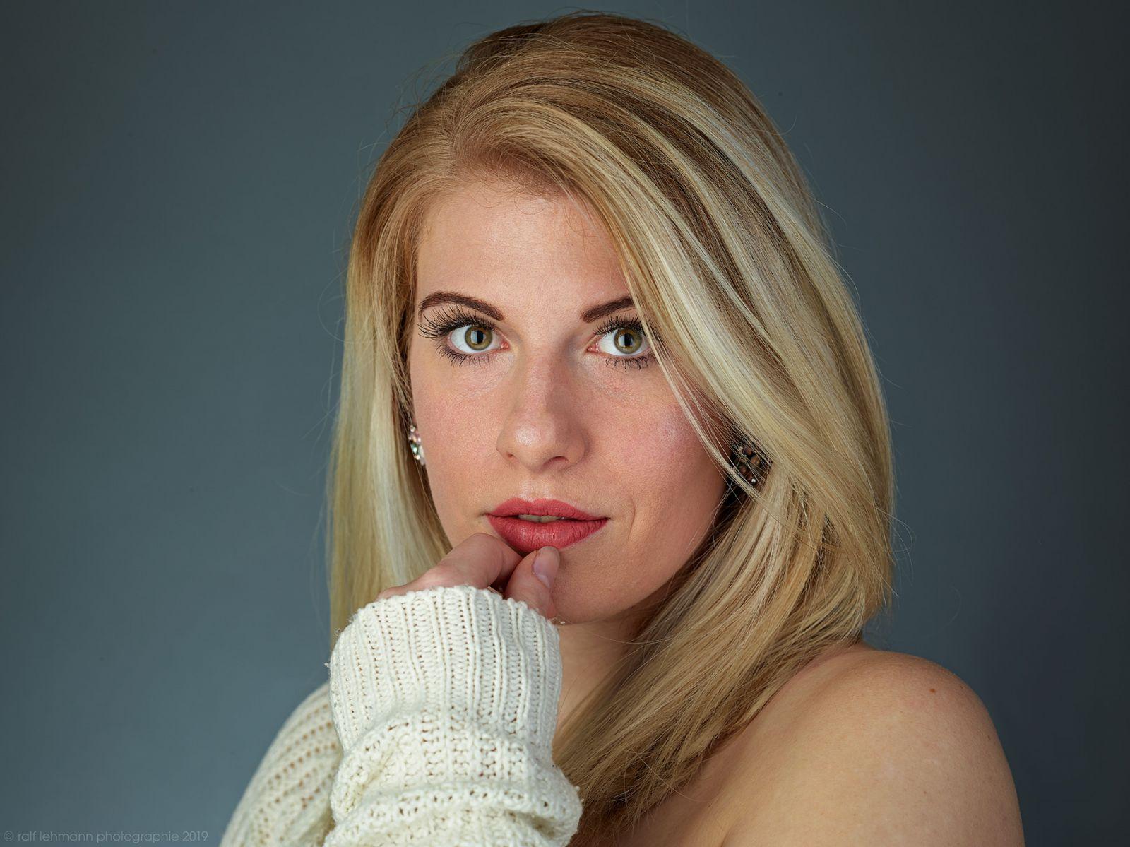 Portrait einer jubgen blonden Frau mit einem weissen Pullover. Entstanden in Köln.